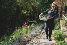 Blonde Woman Wearing Eyeglasses And Apron Walking On Path In Garden