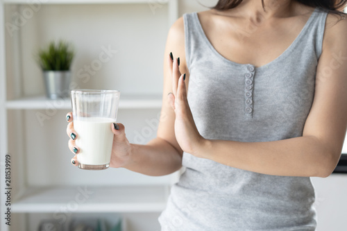 Obraz lactose intolerance concept. Woman holding a glass of milk and having a stomachache. - fototapety do salonu