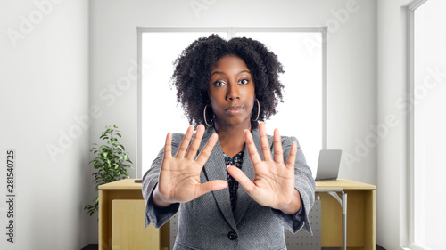 Fotografering  Black African American businesswoman in an office with a stop gesture