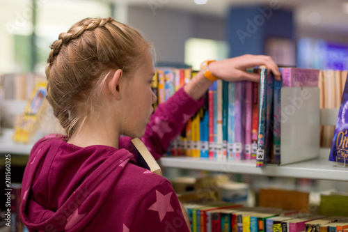 Photographie  A teenage girl with pretty braid blonde hair selecting a book from the booshelf in the library
