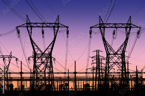 Fotomural  high voltage pylons silhouette , sunset lighting, clear sky background