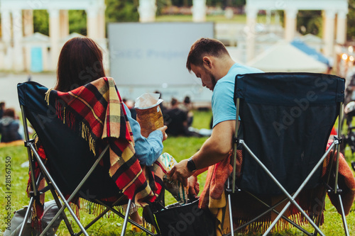 Foto  couple sitting in camp-chairs in city park looking movie outdoors at open air ci