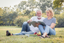 Grandfather And Grandmother Read A Book Sitting On The Grass.
