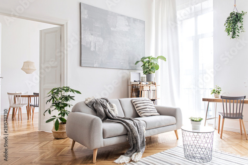 Obraz Stylish scandinavian living room with design furniture, plants, bamboo bookstand and wooden desk. Brown wooden parquet. Abstract painting on the white wall. Nice apartment. Modern decor of bright room - fototapety do salonu