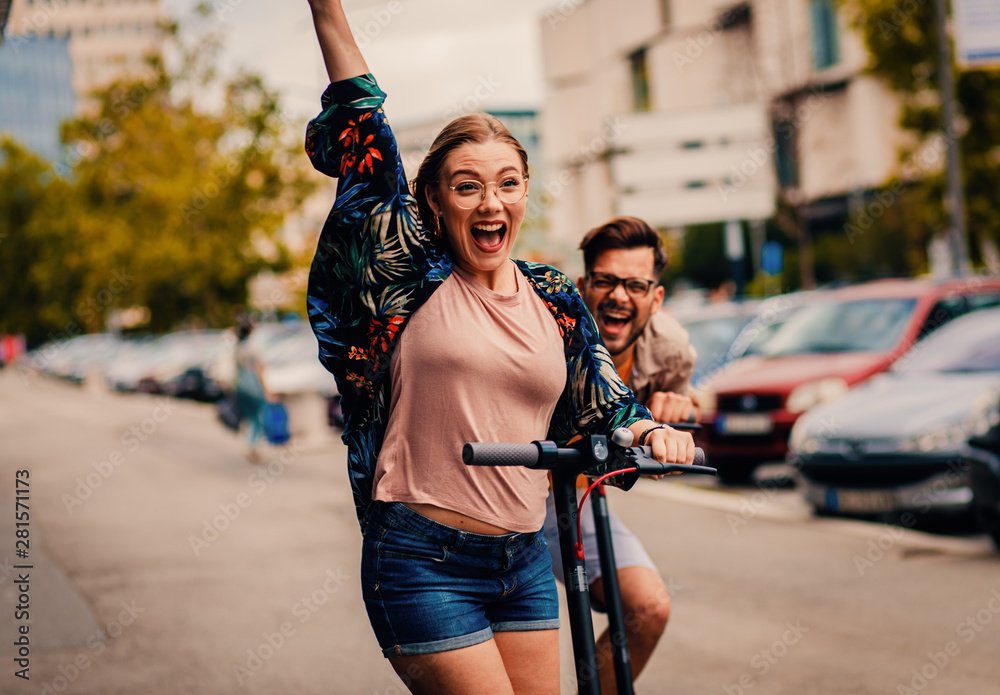Fototapety, obrazy: Young couple on vacation having fun driving electric scooter through the city.