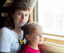 Train Departing From Station. Little Child Girl And Her Mother Looking Through The Window In Train.