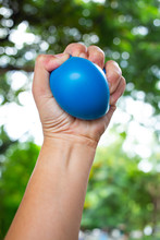 Woman's Left Hand Squeezing Blue Stress Ball On Bokeh Green Garden Background, Exercise And Massage Concept