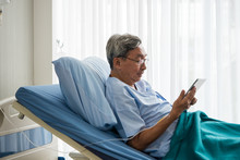 Happy Elderly Patient Sitting On Bed And Making Video Call With Tablet At Hospital.