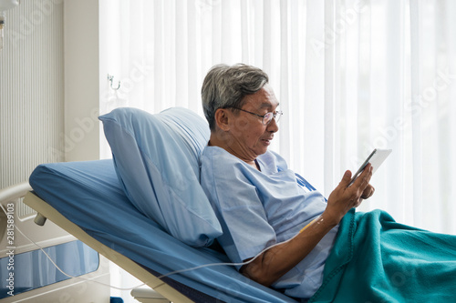 Tela Happy elderly patient sitting on bed and making video call with tablet at hospital