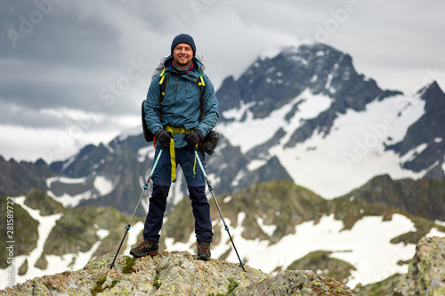 Fototapeta Hiker man stands on the cliff against the top of a mountain. Man has a backpack and trekking poles. Mountain trekking. Copy space obraz na płótnie