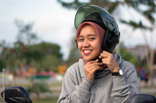 Fotografía  portrait of hijab  woman wearing a helmet before riding a motorcycle in a park