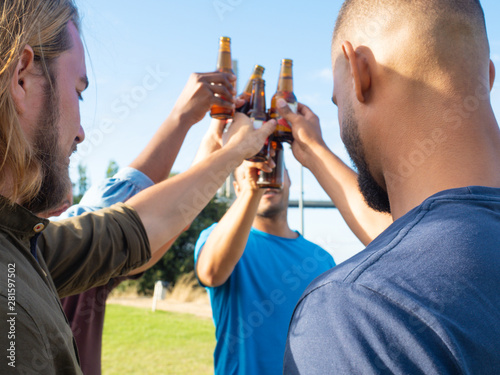 Fototapety, obrazy: Smiling young people clinking beer bottles in park. Happy friends resting in summer park. Concept of celebration