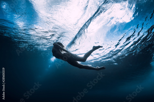 Valokuva  Young woman dive underwater with under barrel wave