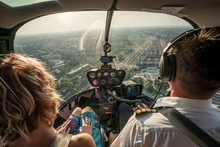 Portrait Of Beautiful Blonde Women And Pilot Enjoying Helicopter Flight. She Is Amazed By Cityscape.