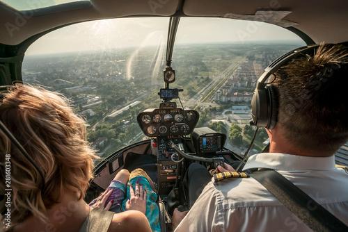 Fényképezés Portrait of beautiful blonde women and pilot enjoying helicopter flight