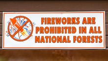 Panorama Fireworks Are Prohibited In All National Forests Sign Against A Wooden Surface