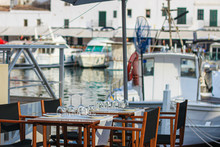 Free Table And Empty Chairs Of Fish Restaurant In The Port Of Ciutadella Town, Menorca, Balearic Islands, Spain