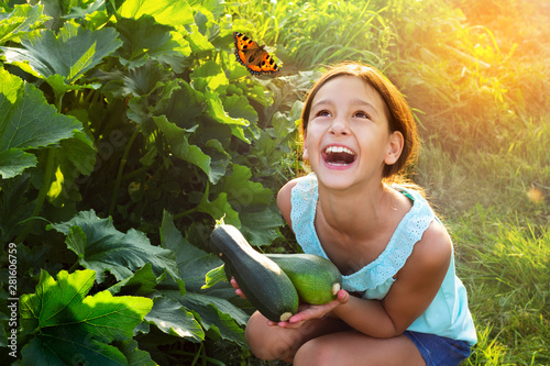 Fotografie, Obraz  Happy laughing girl holding fresh zucchini outdoors in garden looking on flying