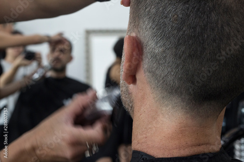 close up of a hairstylist giving man a haircut