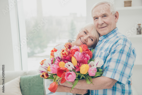 Obraz Closeup photo of two adorable aged people cute pair anniversary holiday surprise big red tulips bunch flat indoors - fototapety do salonu