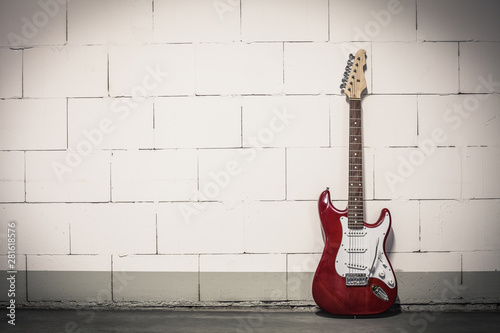 Red electric guitar stands to the right against white brick wall, toned vignette crisp image - 281618576