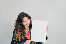 Girl Holding A Blank Empty Canvas Board In Her Hands And Smiling. Copy Space. European Young Woman Looking At Mockup Poster.