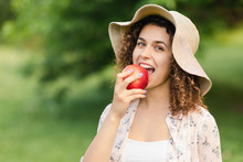 Beautiful Girl In A Hat Eats An Apple On Nature