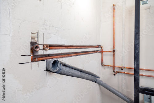 Fotografia  Closeup many new sewer copper and plastic pipes, fittings on concrete wall