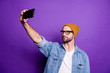 Leinwanddruck Bild Photo of cool guy holding telephone taking selfies for instagram blog wear denim outfit isolated violet background