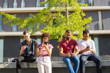Four Friends Totally Excited With Their Mobile Phones. Men And Woman Standing Outside, Sitting On Parapet And Using Smartphones. Internet Addicted Concept