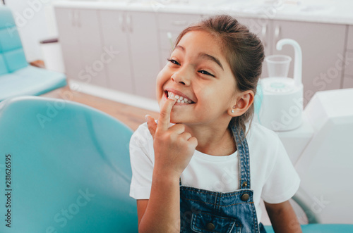 Leinwand Poster  Mixed race little patient showing her perfect toothy smile while sitting dentist