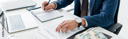 Fototapeta top view of businessman holding pen near contract and money in office obraz