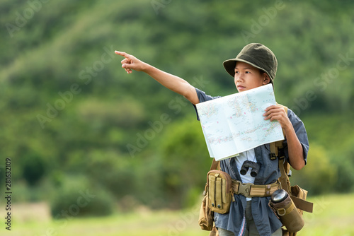 Obraz Asian boy backpack checking map and pointing in jungle forest, trips adventure and tourism for destination and leisure for education and relax in nature park .  Travel vacations Concept - fototapety do salonu