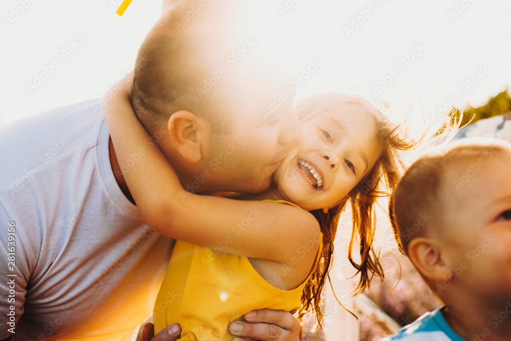 Fototapety, obrazy: Portrait of a beautiful little girl laughing while being kissed and embraced by her father against sunset outside.