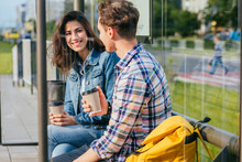 Positive Relax Couple Traveler Drinking Coffee Outdoor At Stop While Waiting Tram, Sits On Bench At Sunny Morning.