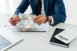 selective focus of man holding folder with money near contract with pen