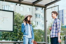 Love At First Sight Concept. Man And Woman Likes Each Other. Man And Brunette Girl Stopped To Get Acquainted. Casual Encounter, Meet On Sunny Summer Day At Bus Stop