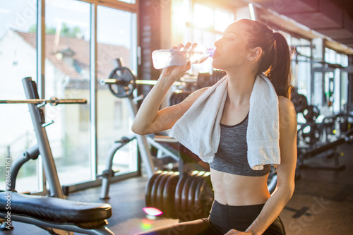 Fotografia  Beautiful young sportswoman with towel around her neck drinking water after spor