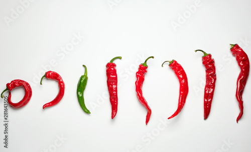 whole ripe red hot chili peppers on a white background, one green