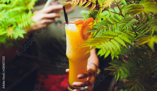 Fotografie, Obraz  Woman hand holding orange cocktail decorated with mint in highball glass