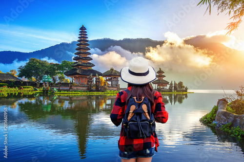 Photo Woman traveler with backpack looking to pura ulun danu bratan temple in Bali, indonesia