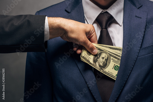 Fotografía  cropped view of man putting cash in pocket of business partner on grey