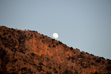 A Full Moon Rises Over The Mou...