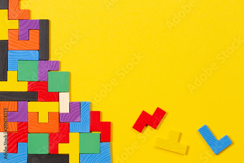 Fotografía  Different colorful shapes wooden blocks on yellow background