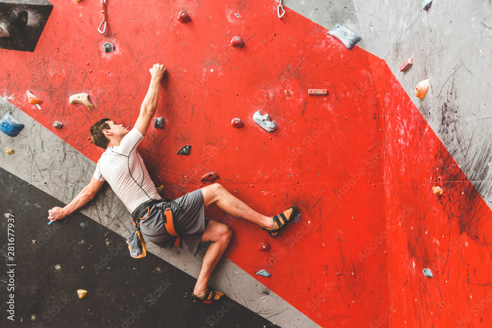 Fototapety, obrazy: Sportsman climber moving up on steep rock, climbing on artificial wall indoors. Extreme sports and bouldering concept