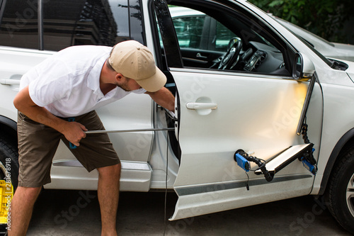 Repairing car dent after the accident by paintless dent repair - 281678918