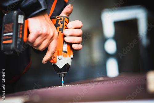 Obraz Worker tightens a screw with an electric screwdriver - fototapety do salonu