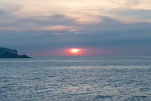 Blue Photo Of A Calm Sea Landscape With Sunset - Cloudy Sky Landscape Over The Sea And A Lighthouse On An Island
