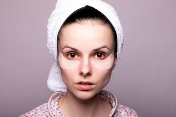 beautiful young woman in a towel on her head and with patches on her face