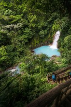 A Young Man Walking Down The Stairs Of The Rio Celeste Waterfall With A Blue Backpack, Alajuela, Costa Rica.